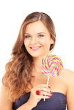 Beautiful female holding a lollipop and looking at camera Royalty Free Stock Image
