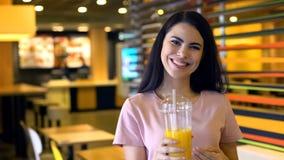 Beautiful female holding orange juice and smiling, fresh bar cocktails, vitamin stock image