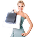 Beautiful female holding shopping bags. Woman isolated on white background, girl buying presents and spending money, seasonal sales Stock Image