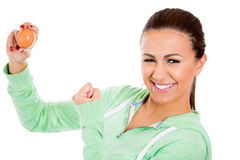 Beautiful female holding up egg in one hand and showing bicep muscle in the other Stock Images