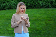 Beautiful female holds cell phone, looking at screen and express Royalty Free Stock Photography