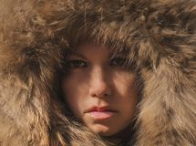 Beautiful girl in a hood with fur of a winter jacket. The girl`s face is hidden in a hood with fur. Stock Image