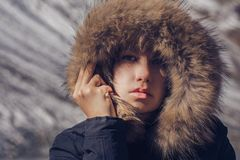 Beautiful girl in a hood with fur of a winter jacket. The girl`s face is hidden in a hood with fur. Royalty Free Stock Photos
