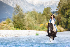 Beautiful Female horse rider crossing river. In a mountainous landscape Royalty Free Stock Photos