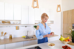 Beautiful female housewife prepares healthy breakfast with smile Royalty Free Stock Photo