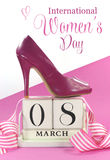 Beautiful female icon pink high heel shoe with vintage shabby chic wood calendar for March 8, International Womens Day Stock Photography