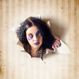 Beautiful female jester breaking out of wallpaper Royalty Free Stock Photo