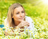 Beautiful female laying on the flower filed Stock Photos