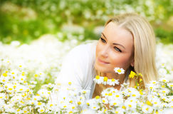 Beautiful female laying on the flower filed Stock Images