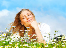 Beautiful female laying on the flower filed Royalty Free Stock Photo