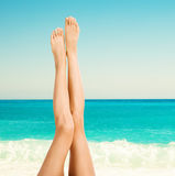 Beautiful female legs against sea Royalty Free Stock Image