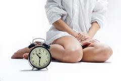 Beautiful female legs and an alarm clock Royalty Free Stock Photo