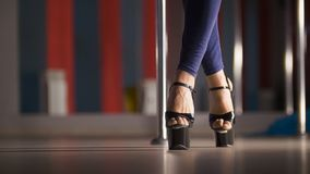 Beautiful female legs in high-heeled shoes dancing on a pole dance in a studio. Close up royalty free stock photography