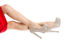 Beautiful female legs in light shoes with rhinestones. Slender legs, high heels, bright sparkling crystals Stock Photo
