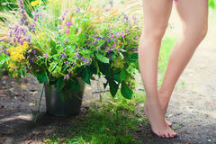 Beautiful female legs next to a huge bouquet   Royalty Free Stock Photos