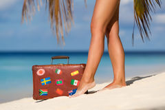 Beautiful female legs with an old suitcase on the beach Stock Image