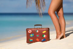 Beautiful female legs with an old suitcase on the beach Stock Photo