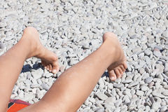 Beautiful female legs on the pebble beach Stock Photo