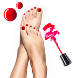 Beautiful female legs with red pedicure and nail polish stock image