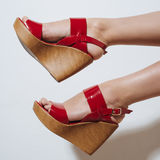Beautiful female legs in red sandals on a wedge Royalty Free Stock Photography