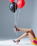 Beautiful female legs in red shoes. And balloons, got hold of the heel shoes royalty free stock photos
