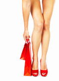 Beautiful female legs, red shoes, shopping concept. Beautiful female legs with red high heels holding shopping bags isolated on white background, money spending Royalty Free Stock Photography