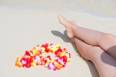 Beautiful female legs on a sandy beach and Hawaiian Lei Royalty Free Stock Photo