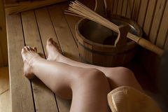 Beautiful female legs in sauna, bath accessories. Wooden bucket and sticks Royalty Free Stock Photo