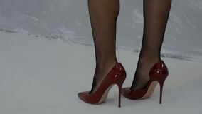 Beautiful female legs in stockings and red high-heeled shoes stock video footage