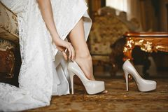 Beautiful female legs in stylish shoes on a high heel, the bride puts on wedding shoes on high heel.  royalty free stock photography