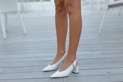 Beautiful female legs in stylish shoes. White fashionable shoes on beautiful female tanned legs on a wooden background stock photos