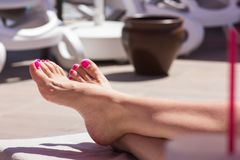 Beautiful female legs sunbathing on a chaise longue royalty free stock images