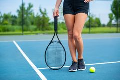 Beautiful woman legs with tennis racket on tennis court. Beautiful female legs with tennis racket on tennis blue court stock photos