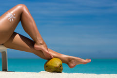 Beautiful female legs in the tropical beach conceptual image of Stock Photography