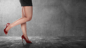 Beautiful female legs wearing high heels in black dress. Standing over city pathway Royalty Free Stock Photography