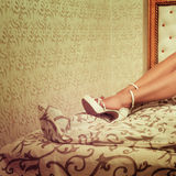 Beautiful female legs in white high heels on bed Royalty Free Stock Photography