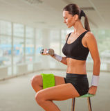 Beautiful female lifting weight and sitting on chair Royalty Free Stock Photo