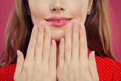 Beautiful female lips with pink color glossy lipgloss makeup. Beautiful female mouth and perfect manicured nails.  stock photography