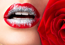 Beautiful female lips with shiny  lipstick and red rose Stock Photography