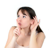 Beautiful female with listening while holding finger on mouth ge Stock Photos