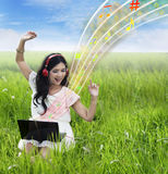 Beautiful female listening to music on laptop - outdoor. Beautiful Asian female is listening to music on her laptop at green field Royalty Free Stock Photos