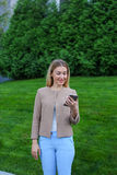 Beautiful female looking at smartphone screen and smiles, stands Royalty Free Stock Images