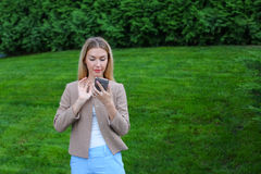 Beautiful female looking at smartphone screen and smiles, stands Royalty Free Stock Photography