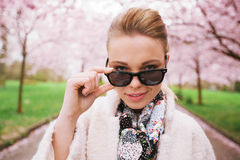 Beautiful female looking through sunglasses at spring park Stock Photography