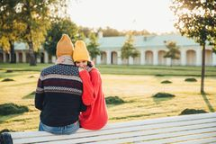 Beautiful female in loose red sweater embraces her boyfriend, missed him too much as didn`t see long ago, sit on bench in park, ha royalty free stock photo