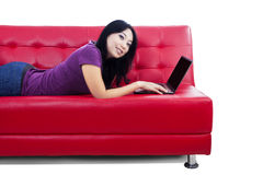 Beautiful female lying on red sofa - isolated Stock Photography