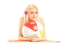 Beautiful female lying on a towel and holding a beach ball Stock Photography