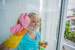 Beautiful female maid doing the housework while using a spray, washing windows Stock Photos
