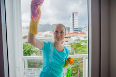 Beautiful female maid doing the housework while using a spray, washing windows royalty free stock photography