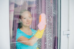 Beautiful female maid doing the housework while using a spray, washing windows Stock Photography